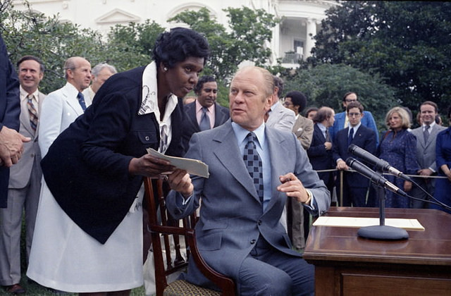 Caption: President Gerald R. Ford approves a seven year extension of the Voting Rights Act, which broadens voting protection especially for Mexican Americans, Asians, and Native Americans while congresswoman Barbara Jordan looks on.