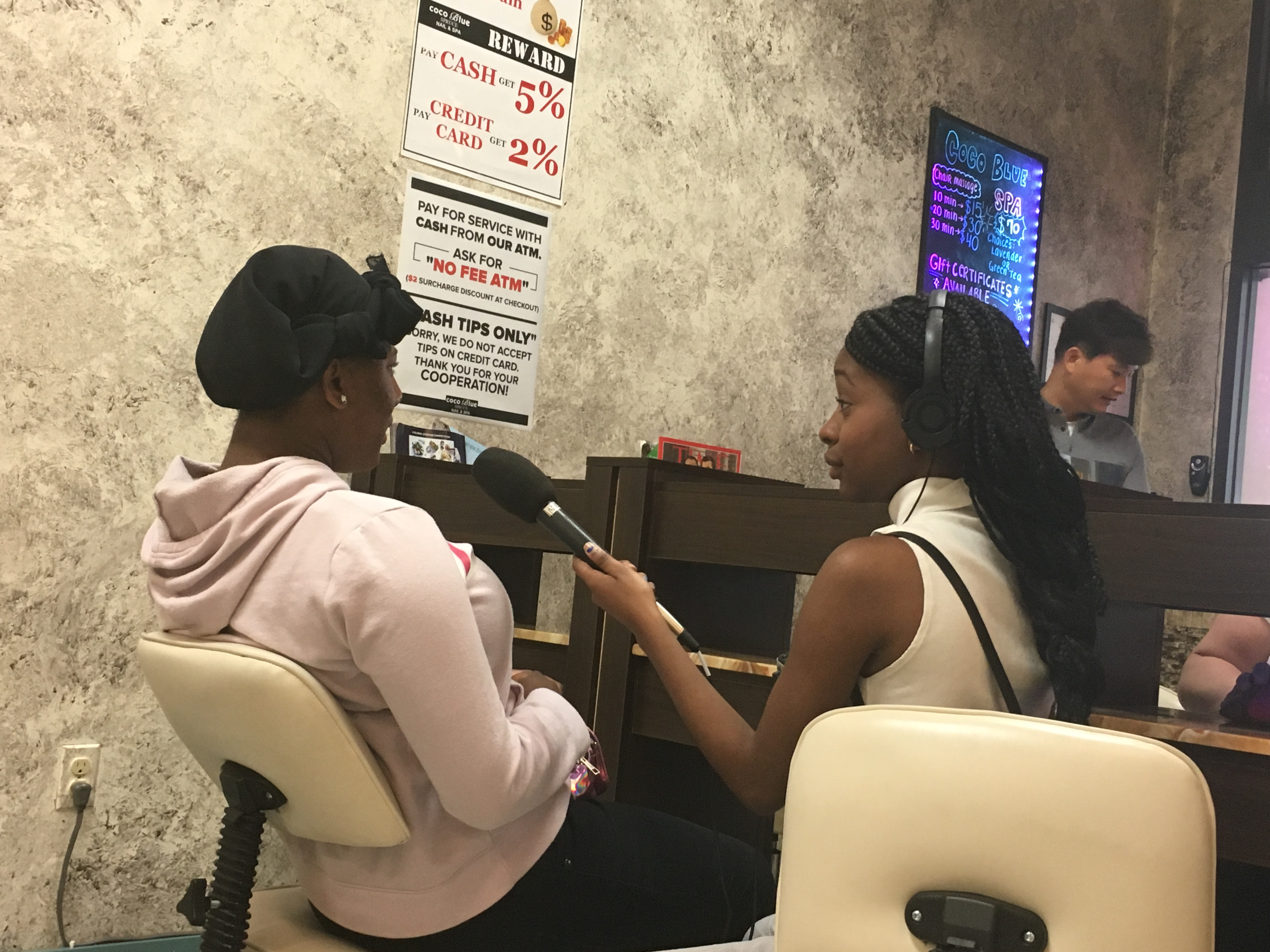 Caption: Youth Producer Derricia Smith sits with program Producer Sandy Fleurimond at a nail salon, Credit: Anne Hoffman