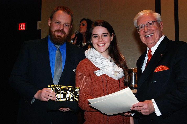 SM East student Anna Karnowski accepts her award from FHSU President Edward H. Hammond, right, and Joel Dugan, assistant professor of art and design.
