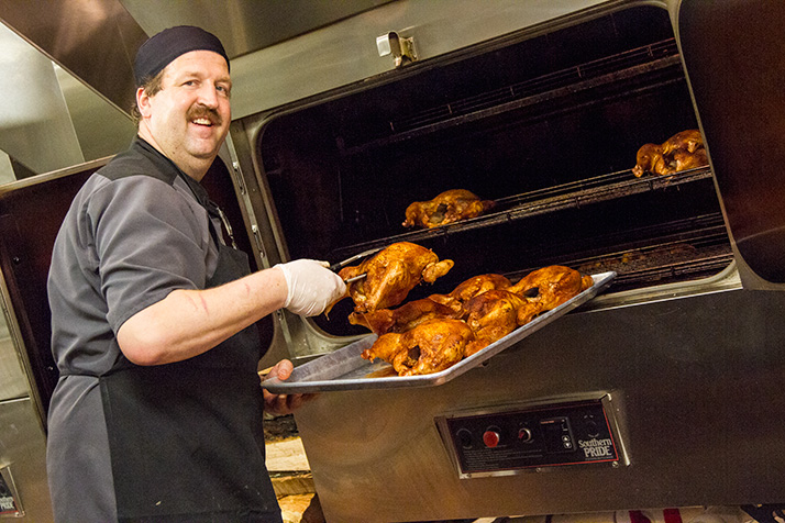 Rob Magee inspecting finishing chickens at his new restaurant, Q39.