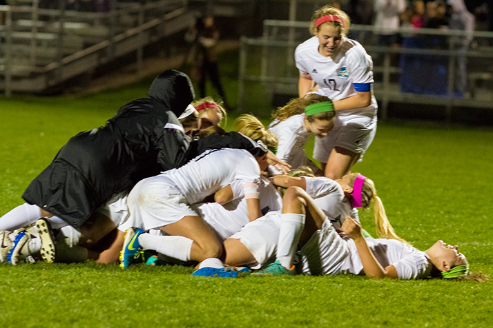 Teammates piled on junior Emma Braasch after her goal with 1:18 left in double overtime secured a 1-0 win for SM East over rival SM West.