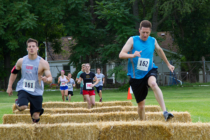Andy Homoly, in blue, and Prairie Village resident Joe Schultz, in grey, hopped over hay bales during Saturday's Stag Steeplechase.