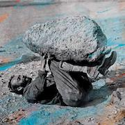 a man on lying his back holds a huge rock above him