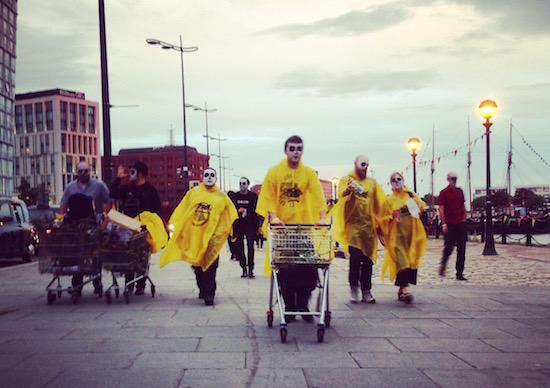 people in yellow ponchos wheel trolleys along a pavement