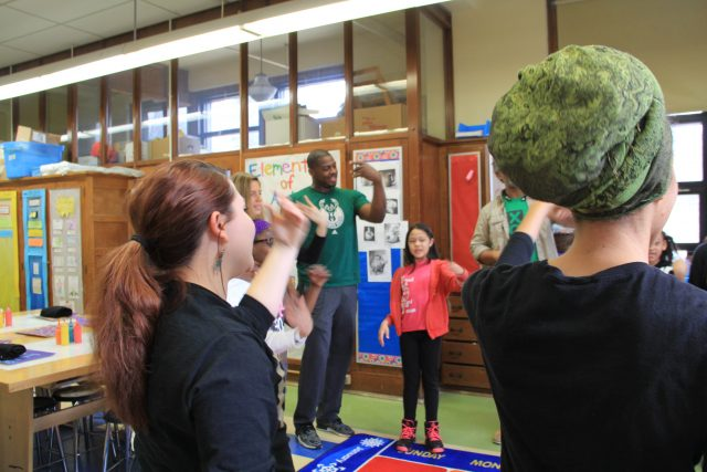 Students warm up with Desmond Mason through dancing before beginning their art projects.