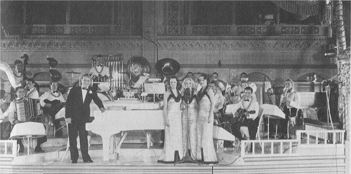 With its leader at the piano and The Debutants (AKA The Three Blue Keys) at the microphone, the Ted Fio Rito Orchestra poses on the stage at the Cocoanut Grove.