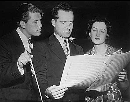 "Gordon MacRae, conductor Carmen Dragon, and vocalist Dorothy Warenskjold review a score for ""The Railroad Hour"" in this 1952 NBC photograph."