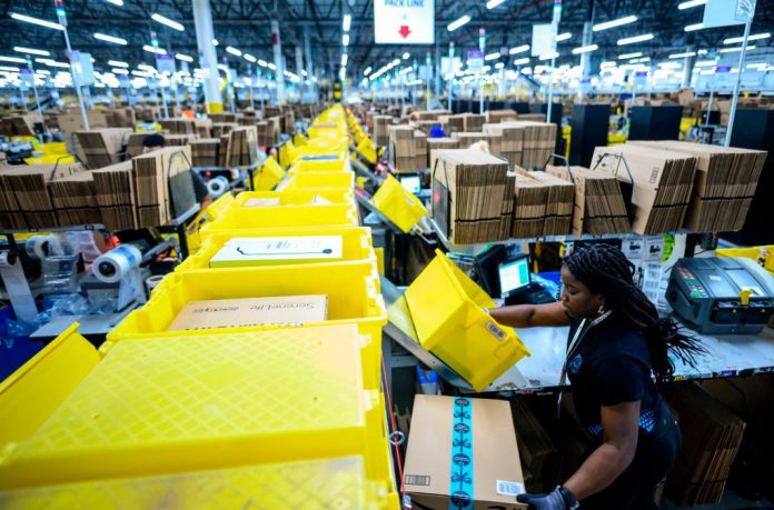A woman works at a packing station at the 855,000-square-foot Amazon fulfillment center in Staten Island, New York City, on February 5, 2019. Photo: Johannes Eisele/AFP/Getty Images