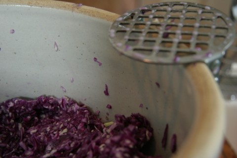 crock of cabbage with potato masher