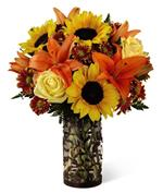 Image of This glass pillar vase, encased in a metal sleeve of lacy forest silhouettes filled with some of the season's sunniest blossoms –sunflowers, yellow roses and spicy orange Asiatic lilies are beautifully combined with burgundy daisy pompons in a hand-arranged bouquet that evokes dreams of a weekend in the country.