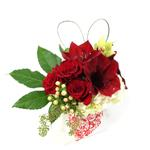 Image of Scarlet Roses and Amaryllis arranged with fatsia and cymbidium orchids on a cloud of hydrangeas in a white ceramic cube container emblazoned with a scarlet heart.