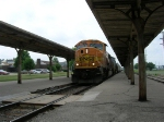 BNSF 8834 leading coal train past passenger platforms,