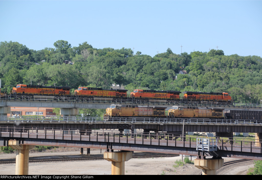 UP 7171 Heads a WB empty coal while a BNSF stack heads east above it.