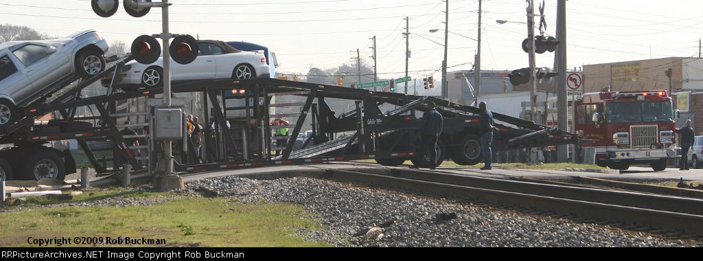 Amtrak Crescent Near Miss.  Truck's rear axle is airborne, center of trailer is dragging on the pavement, and Amtrak behind it, managed to stop just a few feet short.