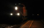 Westbound freight roars through the station on a wet night