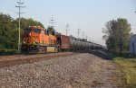 BNSF 8205 New C4 Gevo leads a loaded oil can Sb.