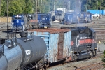 BM 330 enters the yard with a cut of mostly tank cars while other power sits in the background