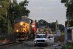 A maintainer waits for track time as Q334-08 rolls east through Seymour