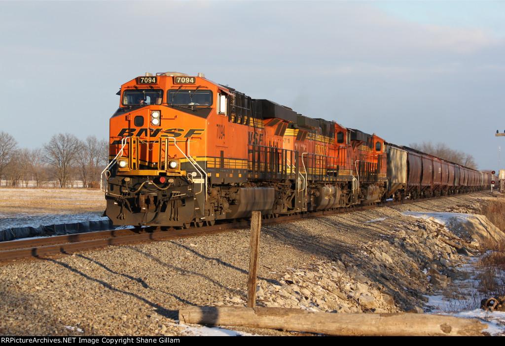 BNSF 7094 Brings a grain train into the setting Sun.
