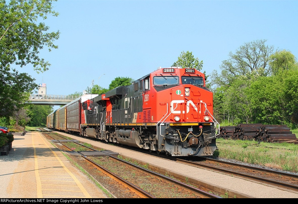 An eastbound mixed freight storms up the bank behind two AC locos