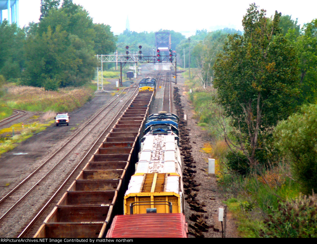 CSX 3165, CSX 398, CSX 239, and another CSX engine stopped at signal in Tifft Yard while the 4 CSX engines go by it
