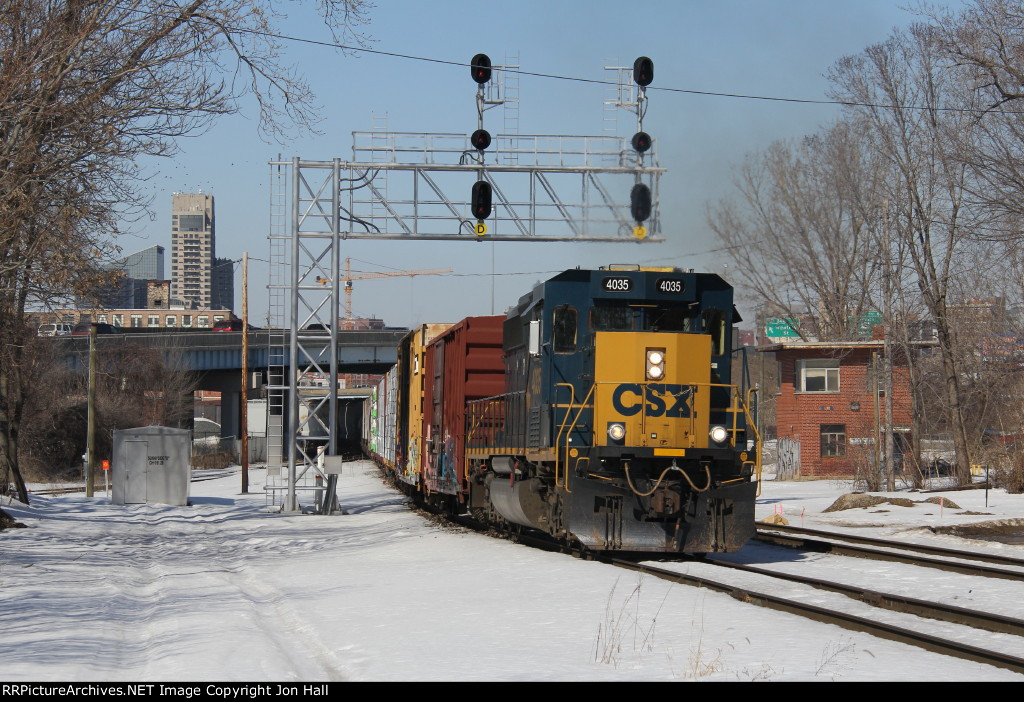 With the old tower at Pleasant St looking on, CSX 4035 starts back east with D707