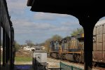 A southbound CSX freight passes the passenger cars and platform of the Historic Railpark and Train Museum