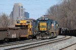 CSX 7515 slowly rolls west past a line of stored equipment to be scrapped