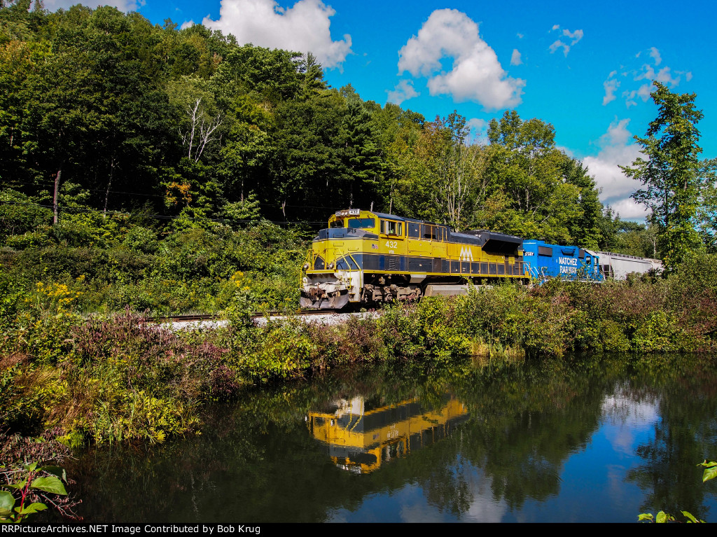 The train is reflected in a pool as it follows Otter Creek