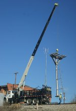 Headless signal mast is moved into position to be lowered.