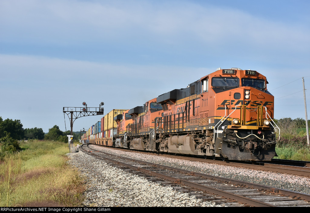 BNSF 7111 screams east with a stack in tow.