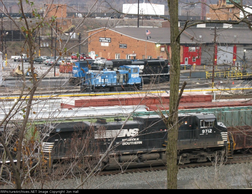Through the trees, NS 9712 passes as 2209 and 2677 wait