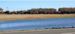 Looking across a pond in Gretna at ballast train 92Q dumping ballast on new double track