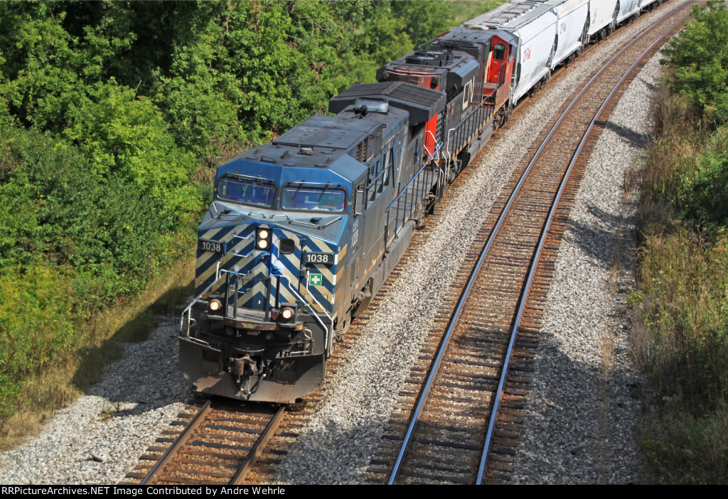 CEFX 1038 and a CN SD70M-2 power a westbound empty grain train