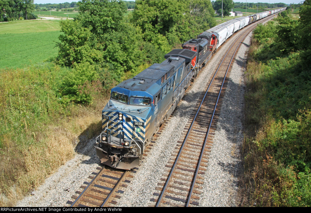 CEFX 1038 and 381's string of grain MTs about to dive under Sauer Road