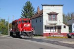 CP 2326 passes a false front building on the corner of Wall St. and 8th