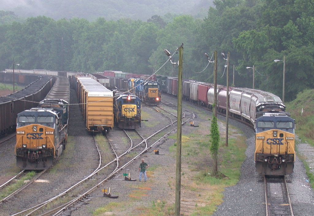 No less than 6 trains are parked in Manchester in the rain waiting for crews