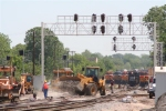 BNSF and UP maintenance forces are busy while trains back up at the IC Crossing.