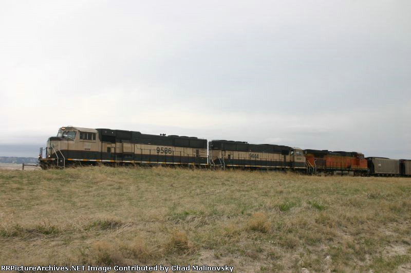 BNSF 9586 east crawls up to the other parked trains