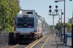 NJT heads east while a couple railfans look on