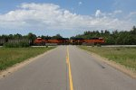 Heading out to the mainline, BNSF 9272 & 9063 pass a crossing with E801