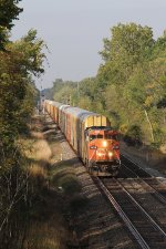 Coming in and out of the morning shadows, E276 heads east with empty autoracks