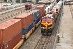 KCS 4584 leads a grain train past a eastbound stack.