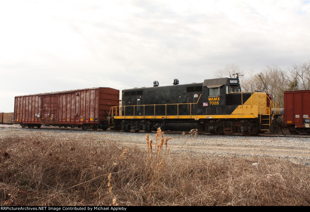 WAMX 7025 posing with a boxcar.