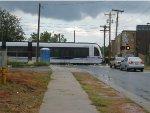 A light rail train crosses an unknown street