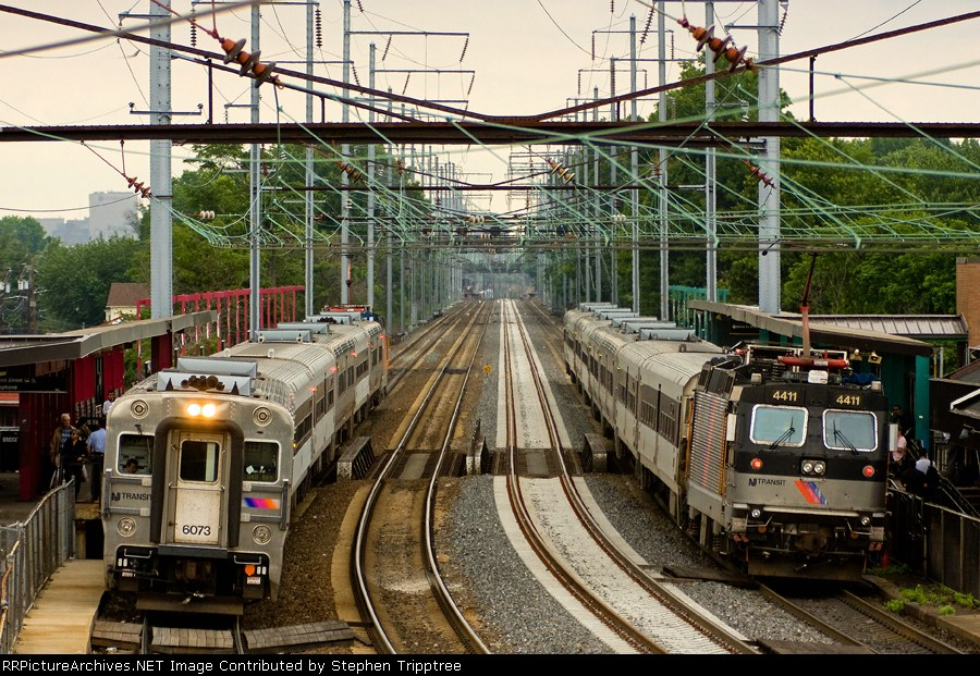 NJT 4411 is departing to head east and into NYP while NJT 6073 is arriving after leaving NYP.