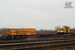 Adzer atop flatcar equipped with unloading ramp stenciled 99057