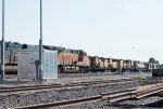 A westbound autorack train passes a rail grinder resting in the siding