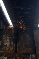 Sparks fall from rail being cut above the next deck sections to be replaced.