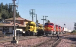 Santa Fe 242 West passes GP30 switchers at station